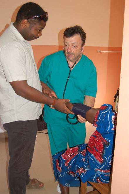Stefano aiutato da Don Romain misura la pressione ad una donna
